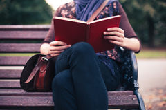 Lectura de la mujer joven en banco de parque Imagen de archivo libre de regalías