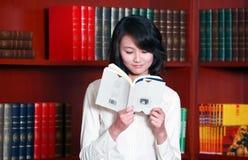 Lectura de la mujer joven en biblioteca Imagen de archivo libre de regalías