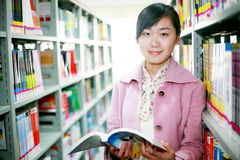 Lectura de la mujer joven en biblioteca Imágenes de archivo libres de regalías