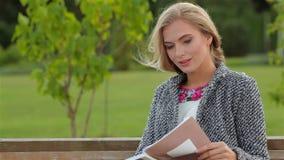 Lectura de la mujer joven en el banco almacen de video