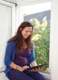 Lectura de la mujer joven en la tableta digital Imagenes de archivo