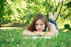 Lectura de la mujer joven en naturaleza Foto de archivo libre de regalías