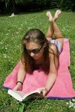 Lectura de la mujer joven en parque imagenes de archivo