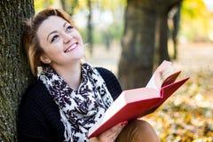 Lectura de la mujer joven en parque del otoño Imagenes de archivo