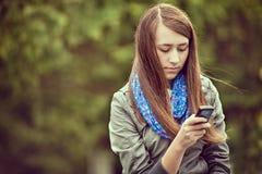 Lectura de la mujer joven SMS en su móvil Fotografía de archivo libre de regalías