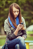 Lectura de la mujer joven SMS en su móvil Fotos de archivo libres de regalías