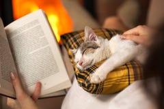Lectura de la mujer por el fuego y confortar su gatito del rescate Fotos de archivo