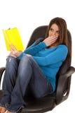 Lectura de la mujer sorprendida en silla Imagen de archivo