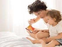 Lectura de la mujer y del bebé en cama Foto de archivo