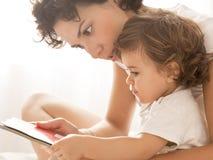 Lectura de la mujer y del bebé en cama Imagen de archivo
