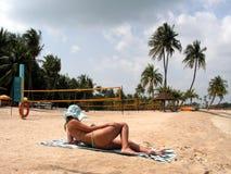 Lectura de la señora en la playa Fotos de archivo