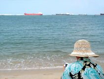 Lectura de la señora por la playa Fotos de archivo libres de regalías