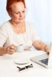 Lectura de la señora mayor su email Imagen de archivo libre de regalías
