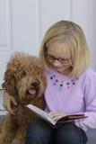 Lectura de la sonrisa de la muchacha con el perro Imagen de archivo libre de regalías
