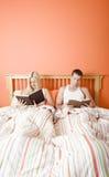 Lectura de los pares en cama Foto de archivo