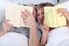 Lectura de los pares en cama Imagen de archivo libre de regalías
