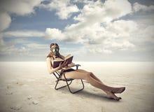Lectura de un libro en el desierto fotografía de archivo libre de regalías