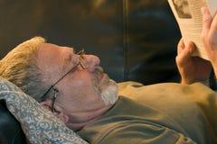 Lectura de un libro en el sofá Fotos de archivo libres de regalías