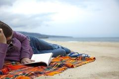 Lectura de un libro en la playa Imagenes de archivo