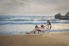 Lectura de un libro en la playa fotos de archivo