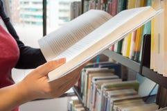 Lectura de un libro en una biblioteca Imagen de archivo