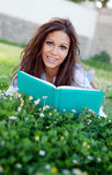 Lectura de un libro que miente en la hierba Imagen de archivo libre de regalías