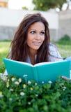Lectura de un libro que miente en la hierba Fotos de archivo libres de regalías