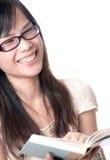 Lectura de un libro y risa Foto de archivo libre de regalías
