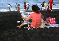 Lectura de una playa que se sienta del periódico Fotos de archivo