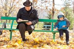 Lectura del abuelo y del nieto en el sol Foto de archivo