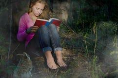 Lectura del adolescente en bosque de niebla fotos de archivo