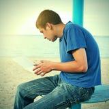 Lectura del adolescente en la playa Fotos de archivo libres de regalías