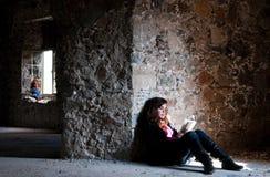 Lectura del adolescente en un cuarto abandonado. Foto de archivo