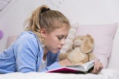 Lectura del adolescente en una cama Imagenes de archivo