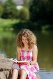Lectura del adolescente por el lago Foto de archivo