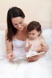 Lectura del bebé de la madre imagen de archivo libre de regalías