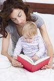 Lectura del bebé y de la mamá en cama Foto de archivo libre de regalías