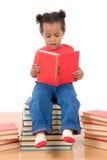 Lectura del bebé que se sienta en una pila de libros Imágenes de archivo libres de regalías