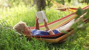 Lectura del bestseller pasado en hamaca acogedora en sombras de los manzanos almacen de metraje de vídeo