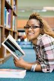 Lectura del estudiante femenino en biblioteca Fotografía de archivo libre de regalías