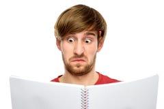 Lectura del hombre algo que parece sorprendido Imagen de archivo libre de regalías