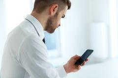 Lectura del hombre de negocios algo en la pantalla de su teléfono celular Fotos de archivo