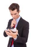 Lectura del hombre de negocios algo en su pista de la tablilla Fotografía de archivo