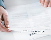 Lectura del hombre de negocios a través de un contrato legal Imagen de archivo libre de regalías
