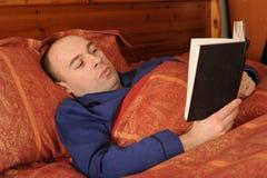 Lectura del hombre en cama Fotos de archivo