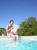 Lectura del hombre en el borde de la piscina Foto de archivo