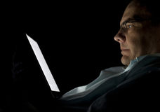 Lectura del hombre en obscuridad de la tablilla Foto de archivo libre de regalías