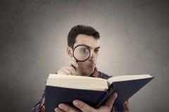 Lectura del hombre joven con una lupa fotos de archivo libres de regalías