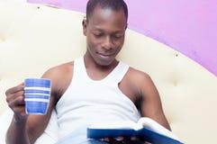 Lectura del hombre joven con una taza de café a disposición Imagen de archivo