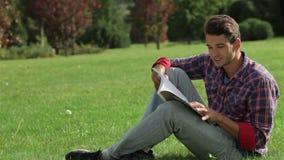 Lectura del hombre mientras que se sienta en la hierba metrajes
